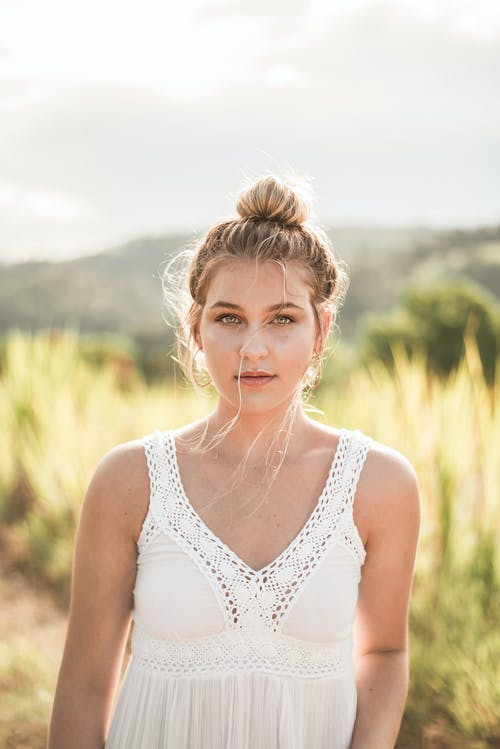 Portrait Photo of Woman in White Sleeveless Top