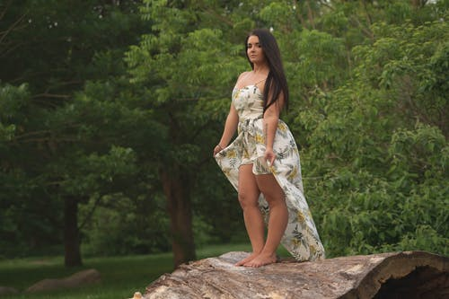 Photo of Woman in White Floral Dress Standing on Huge Hollow Log