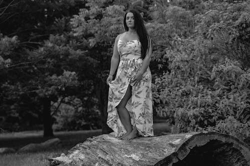 Grayscale Photo of Woman in Floral Dress Standing on Huge Hollow Log