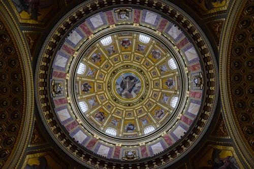 From below majestic interior ornamental dome of St. Stephen Basilica with religious paintings and mosaic elements located in Budapest