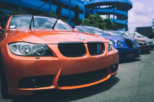 Orange Bmw Car Beside Blue Bugatti Car