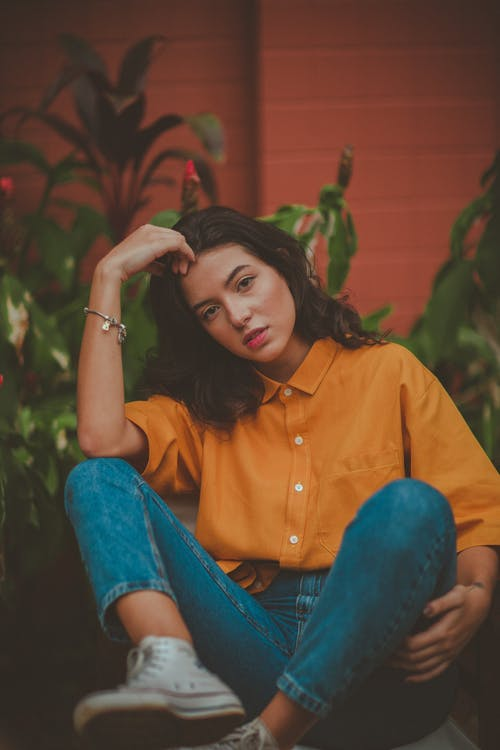 Photo of Sitting Woman in Mustard Shirt and Blue Denim Jeans Posing