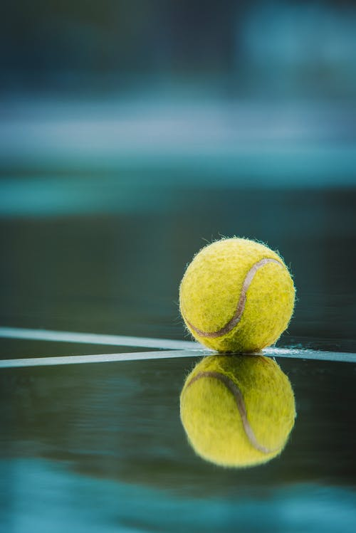 Selective Focus Photography of Tennis Ball on Floor