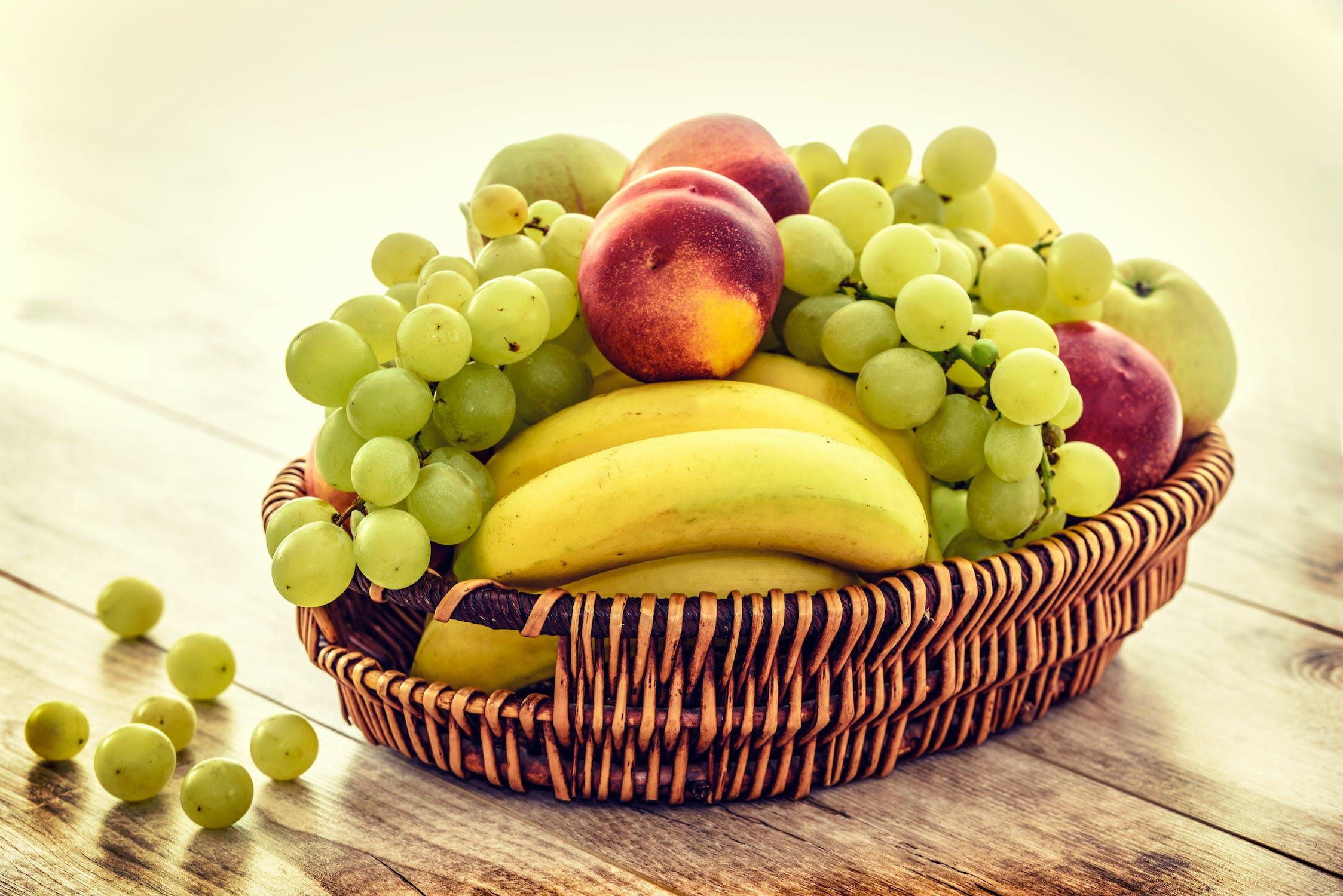 Obstkorb mit Obst aus der veganen Lebensmittelliste: Trauben, Pfirsichen, Äpfeln und Bananen