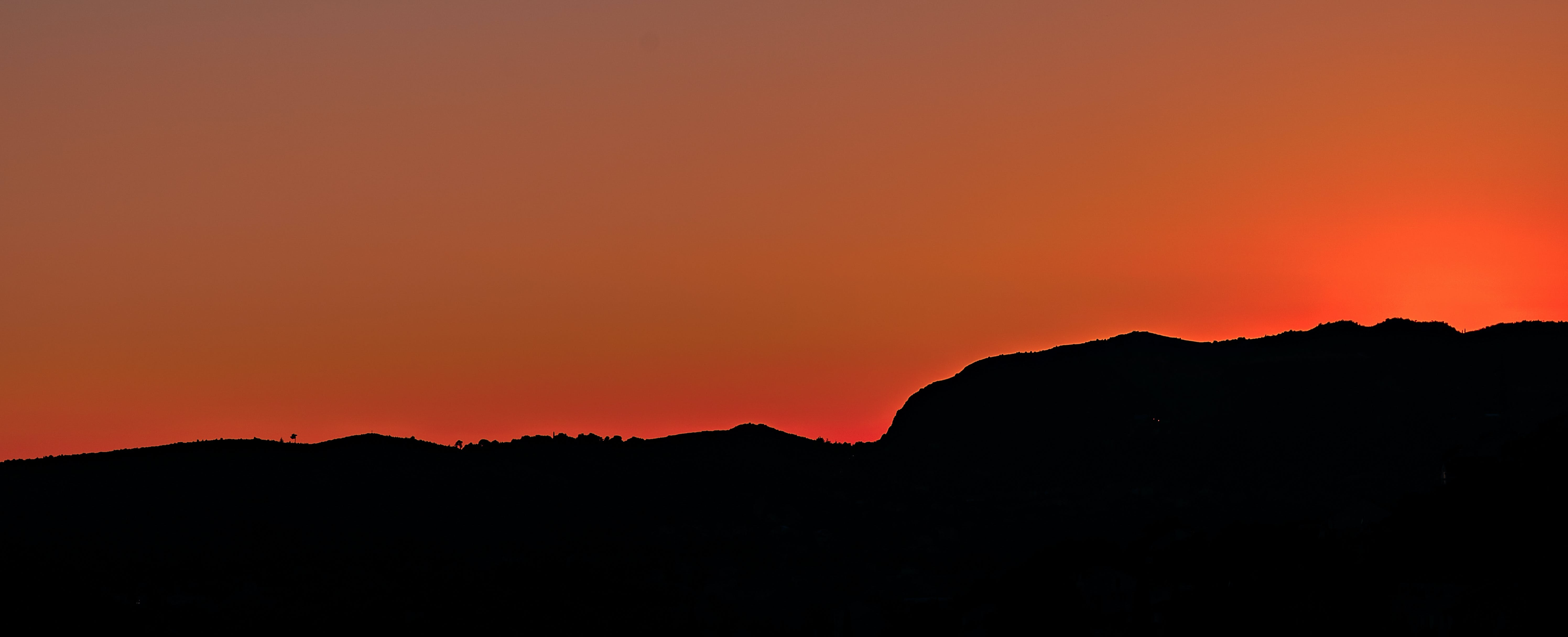 Black Mountain Under Brown Sky during Sunset