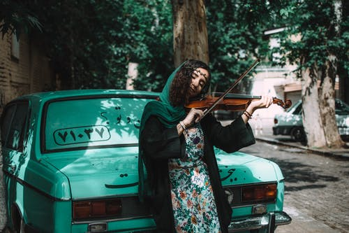 Woman Playing Violin While Leaning On Green Vehicle