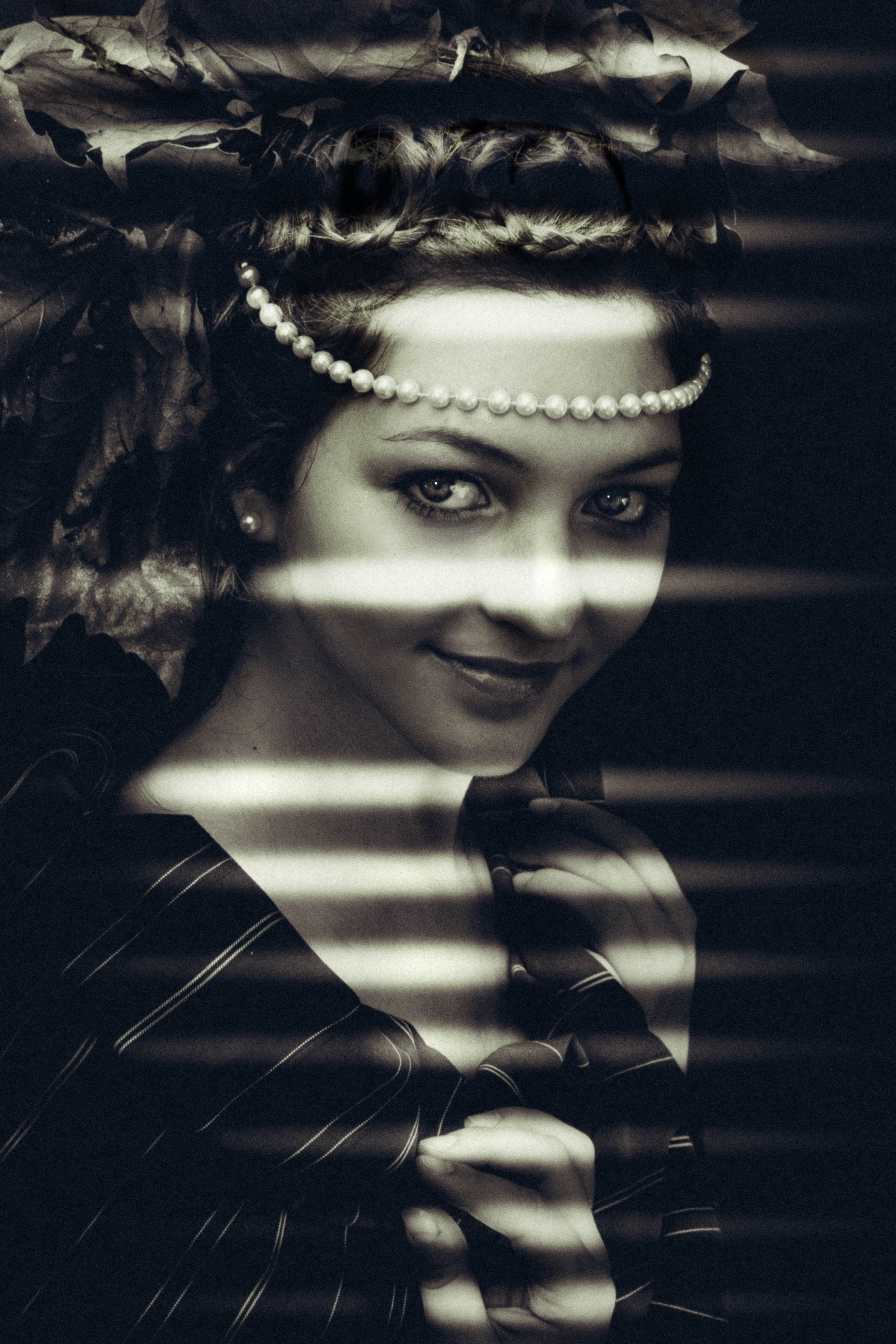 Grayscale Photo of Woman Wearing Pearl Headpiece Inside Dimmed Room