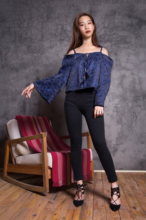 Woman in Blue Off-shoulder Top Standing Near Brown Wooden Rocking Armchair