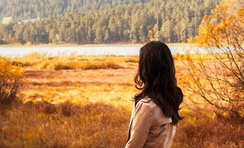 Woman Facing River Between Brown Fields