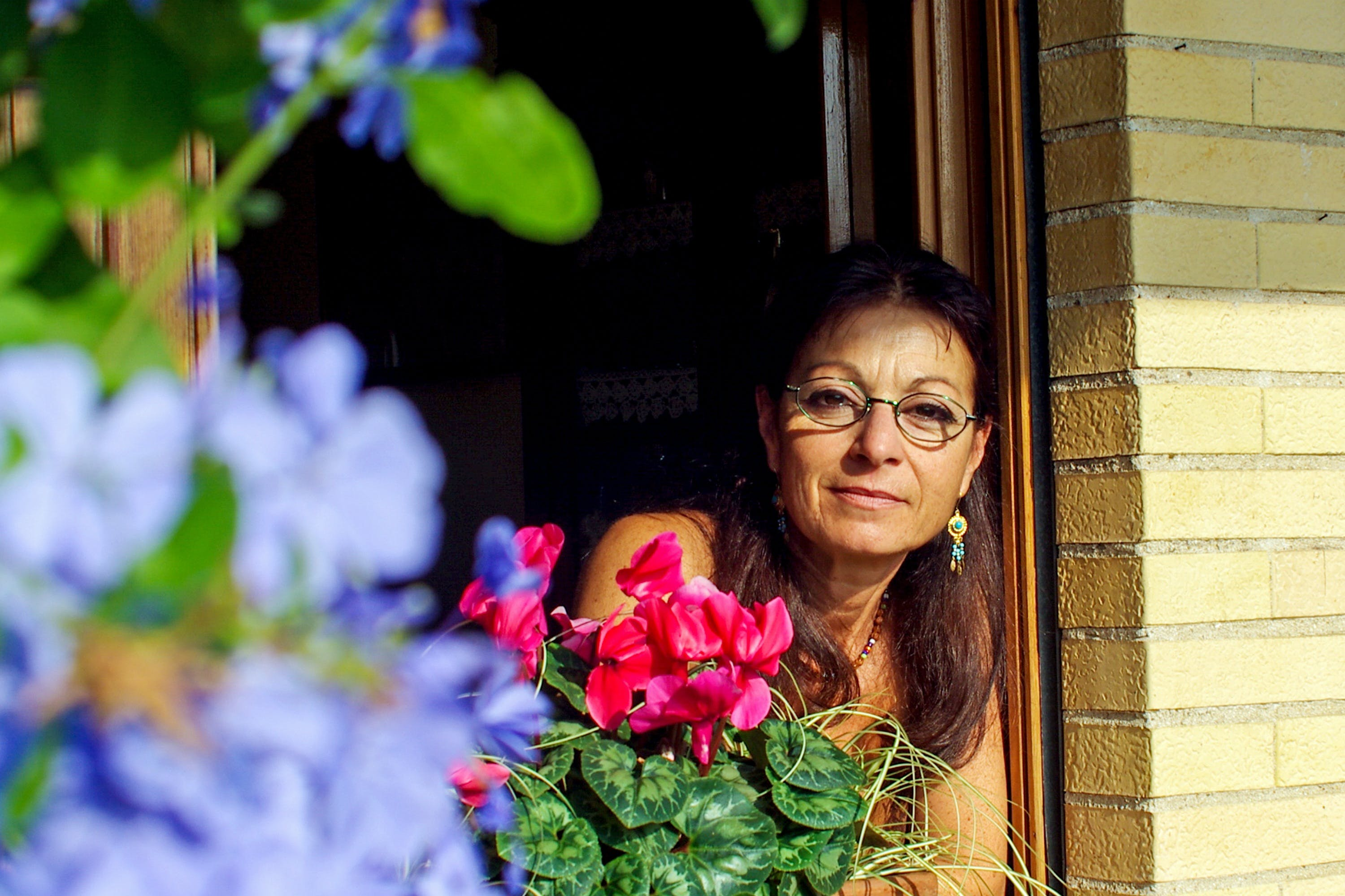 Woman on Window Near Pink Cyclamen and Purple Leadwort Flowers