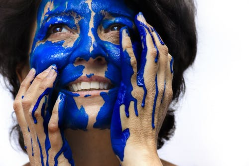 Woman Holding Her Face With Paint