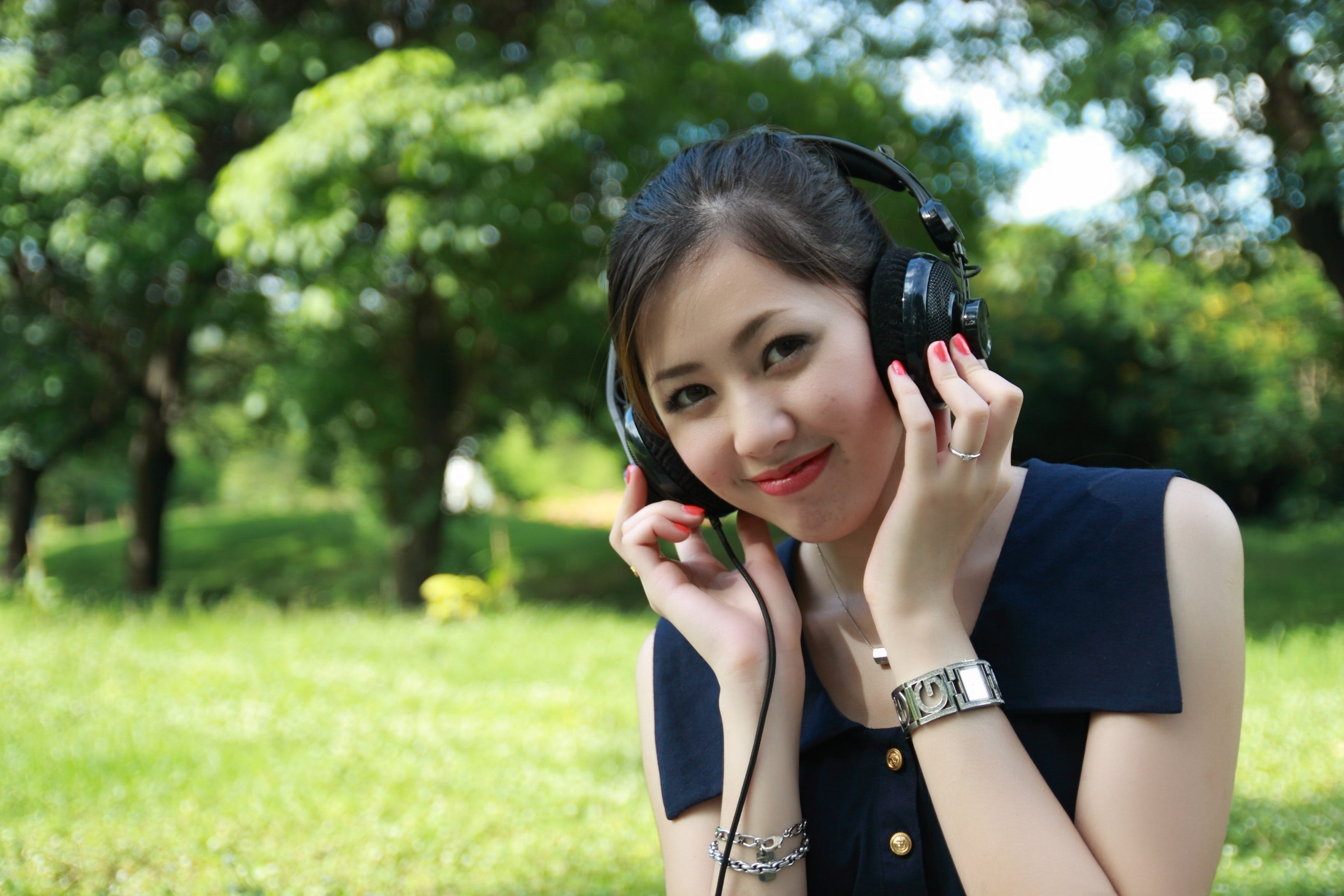 Woman Listens to Earphones in Open Grassfield