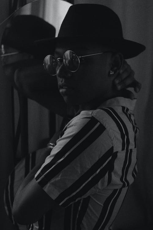Grayscale Photo of Man Wearing Striped Shirt and Fedora Hat