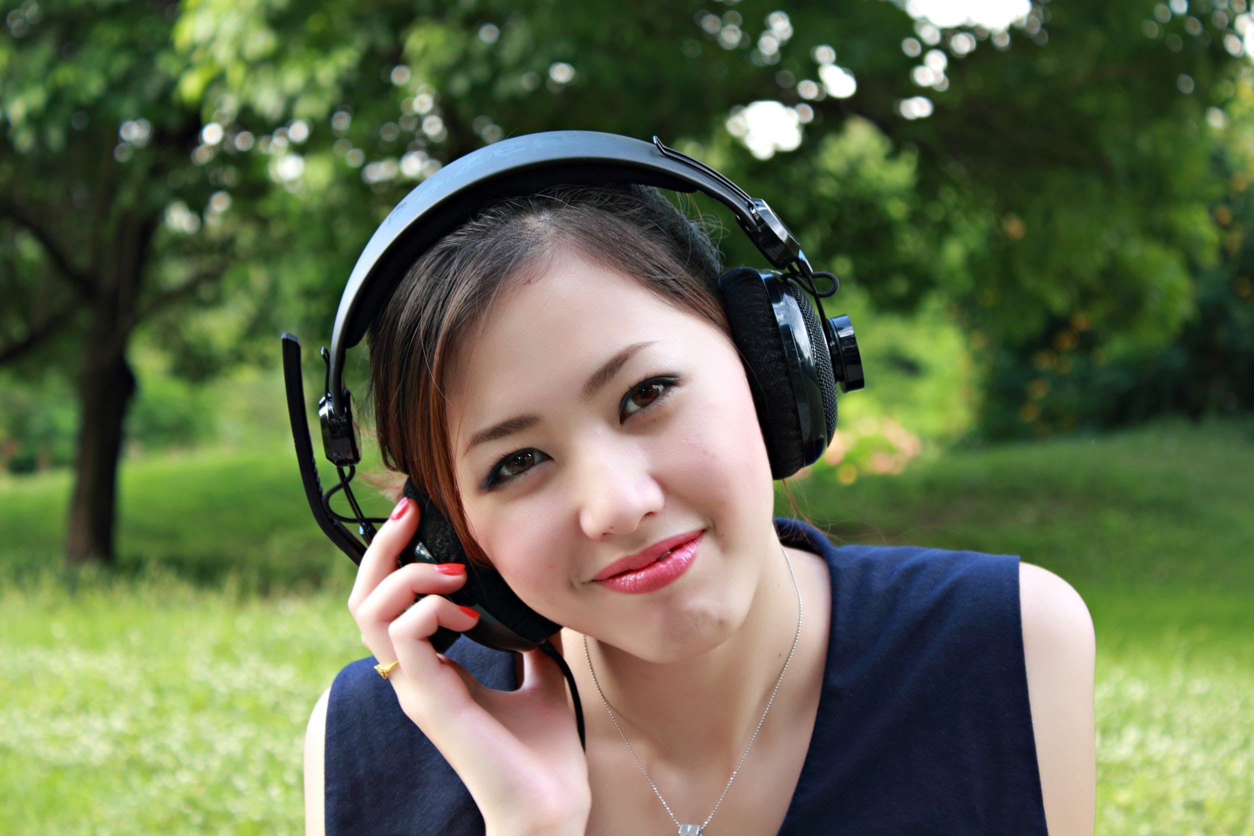Woman Sitting on Ground While Using Headset