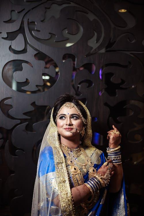 Photos gratuites de femme portant des bijoux en or, femme vêtue d'une robe traditionnelle bleue