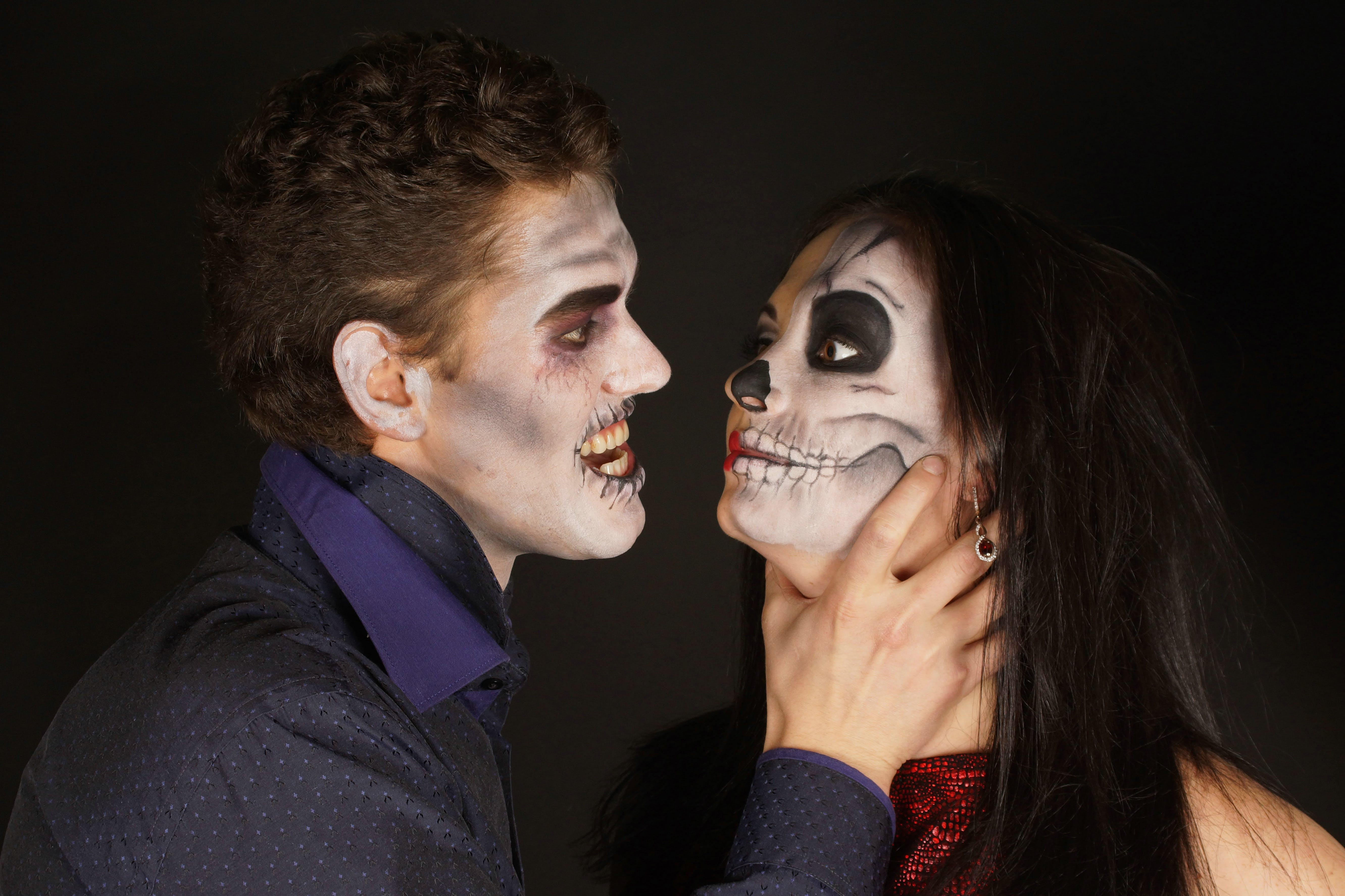 Man With Halloween Skeleton Makeup Choking a Woman With Skeleton Makeup