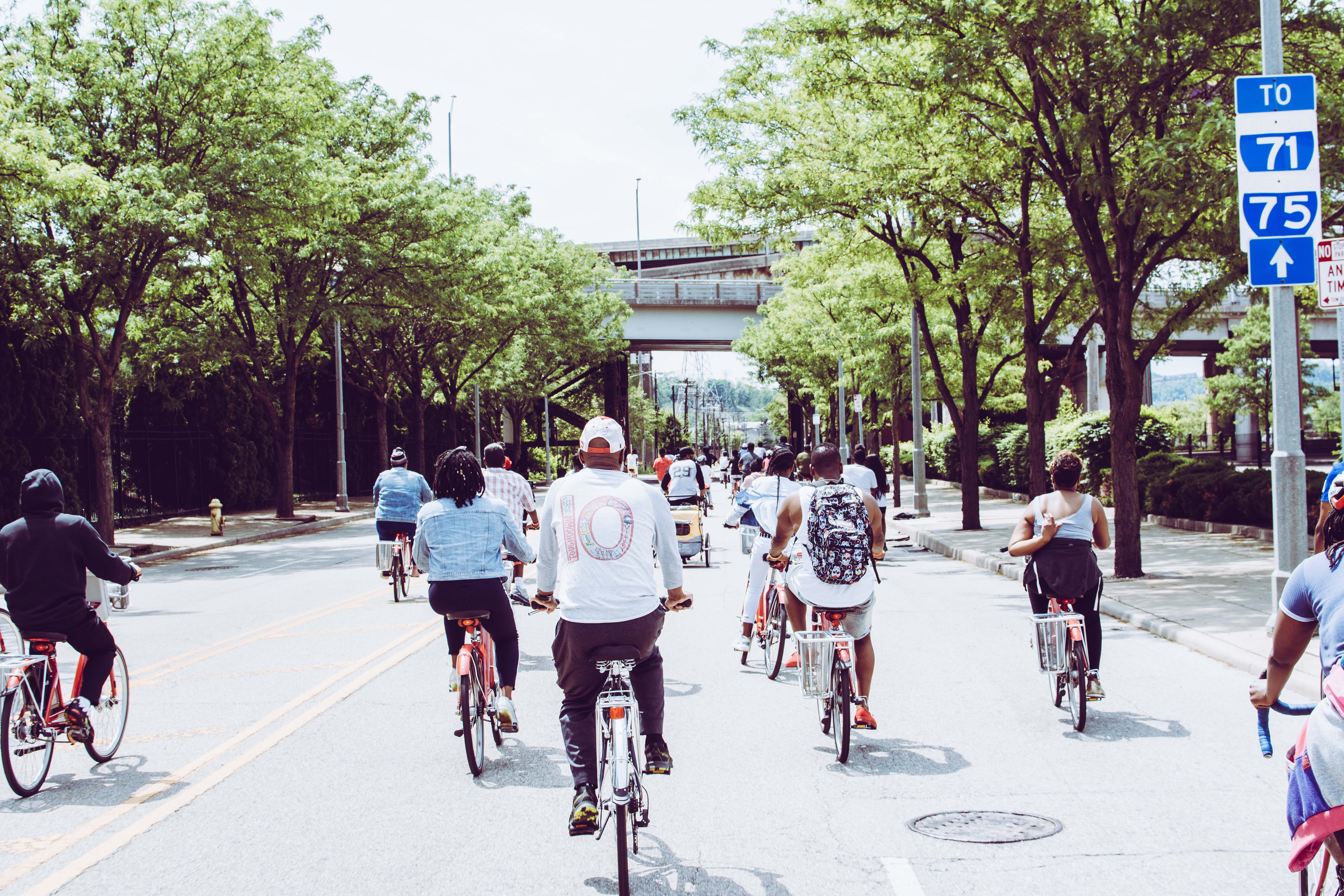 People Riding Bicycle on Concrete Road