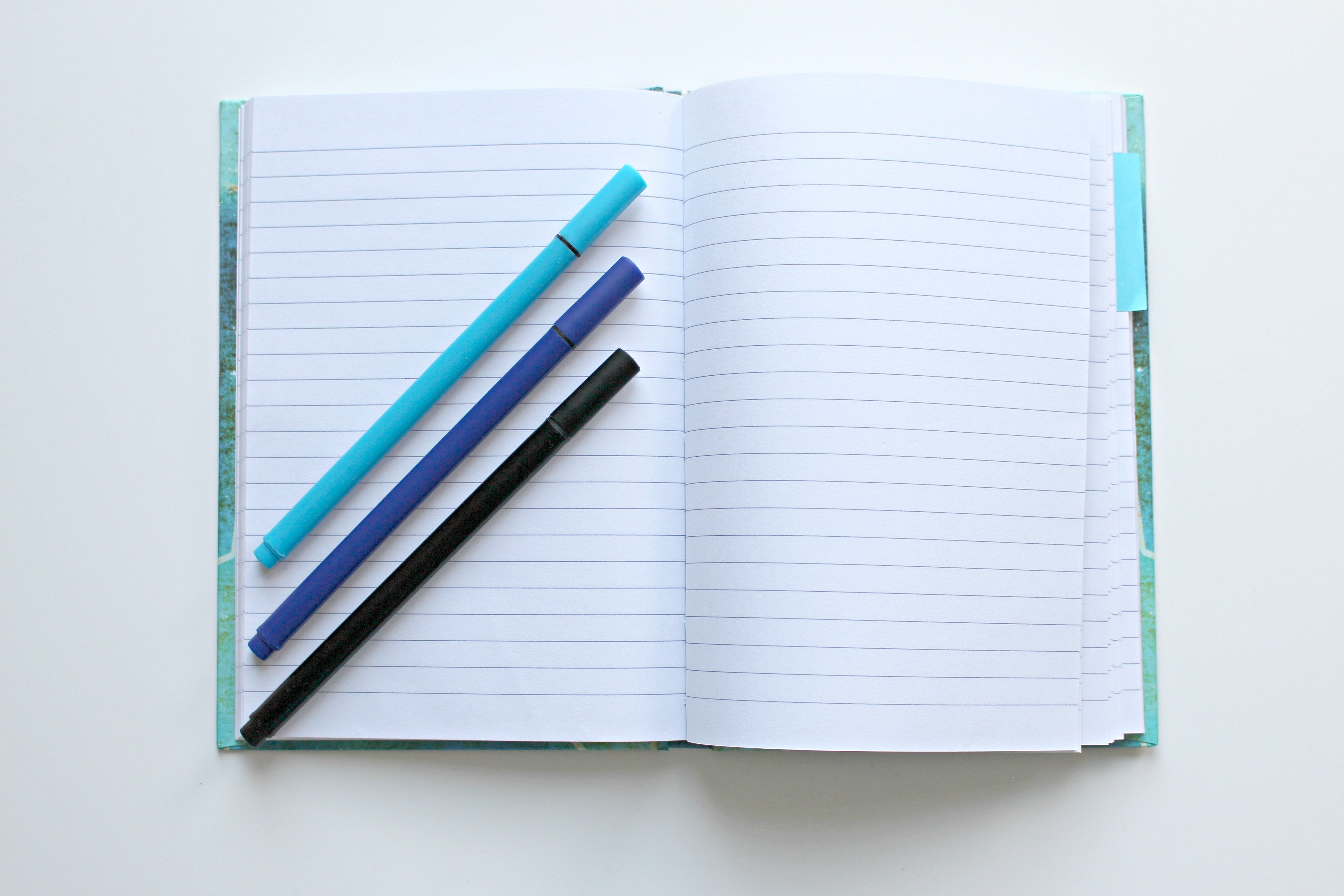 Opened Notebook With Three Assorted-color Pens