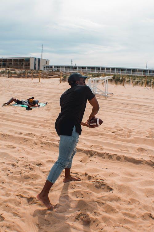 Man Playing Football On Sand
