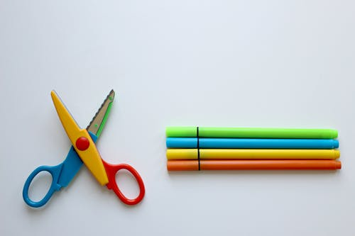Multicolored Scissor and Four Coloring Pen on White Surface