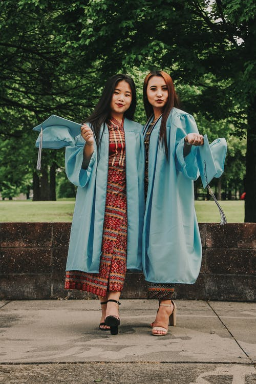 Two Women Wearing Blue Academic Suits Standing Near Trees