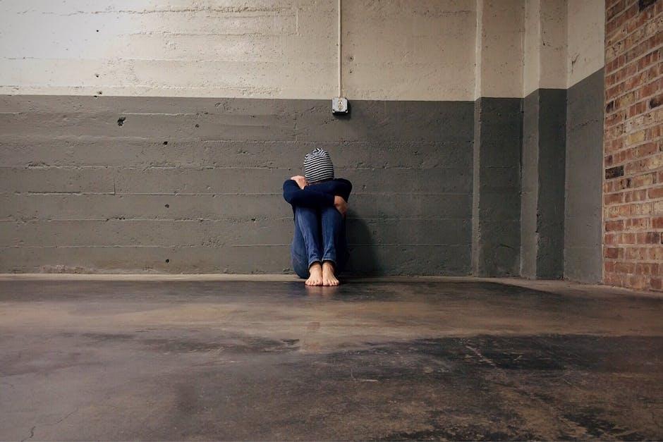 Person Sitting Beside Wall Inside Empty Room