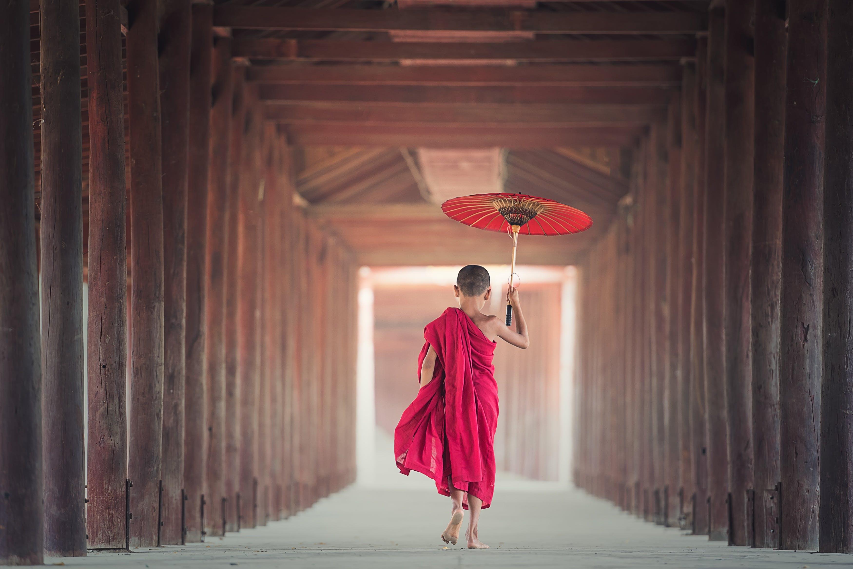 Boy Walking Between Wooden Frame While Holding Umbrella