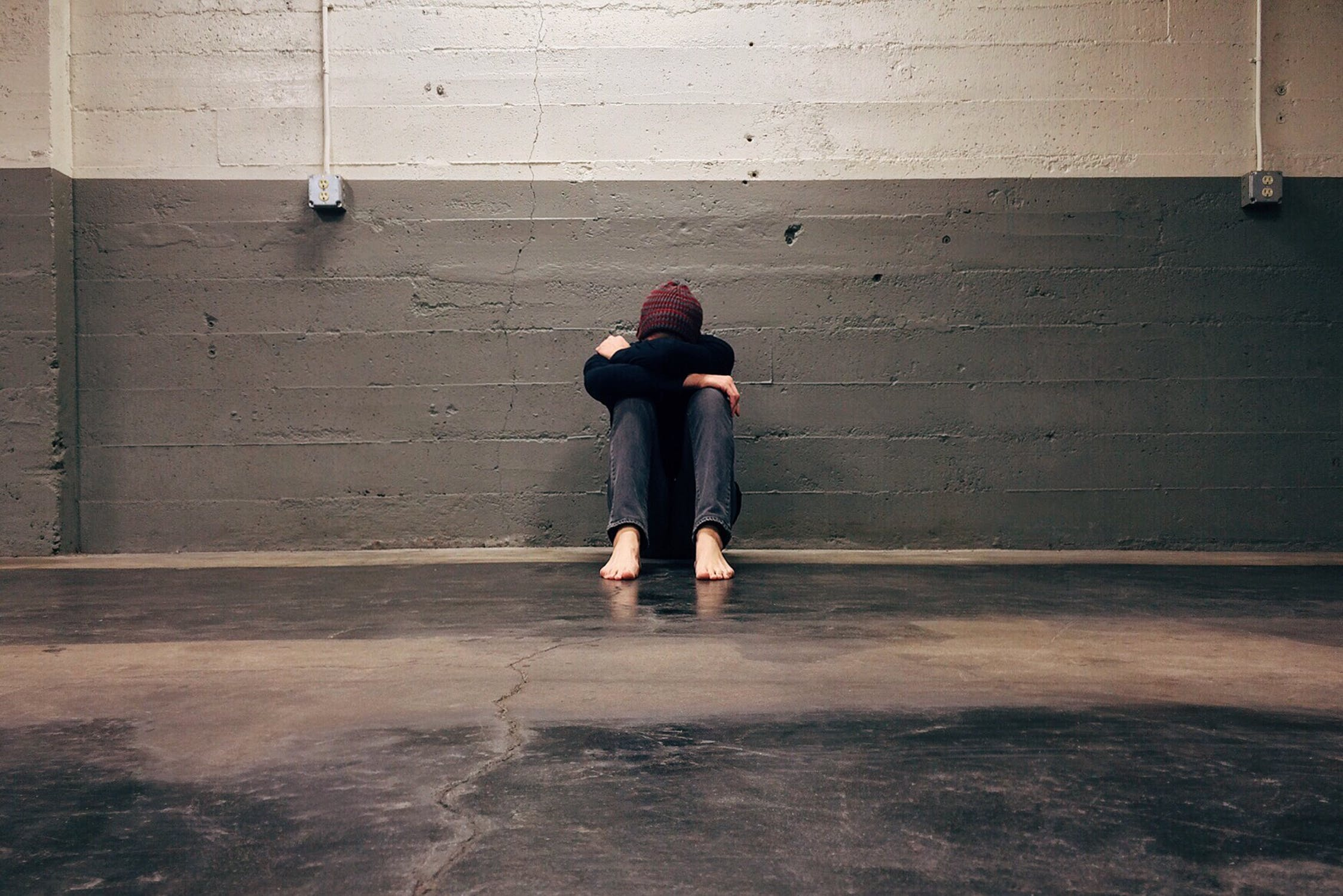 A person sitting on the floor with their head tucked between their knees.
