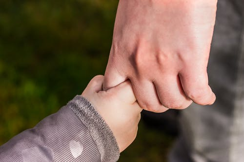 Child Holding Hand of Another Person