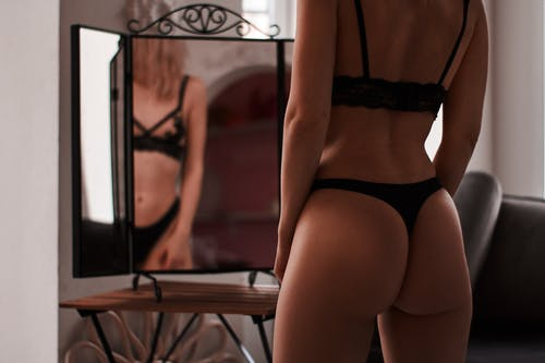 Woman Wearing Black Panty and Bra Standing in front of a Mirror