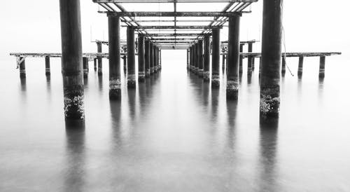 Grayscale Photography of Dock on Body of Water