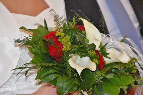 Bride Holding White Calla Lilies and Red Rose Flowers Bouquet