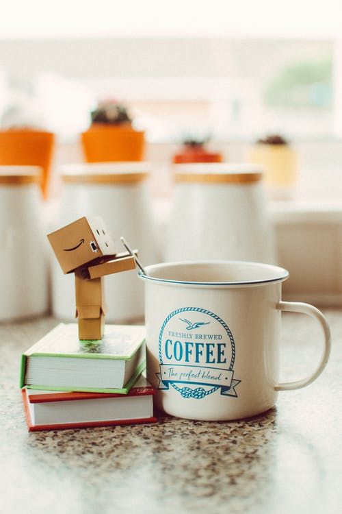 Cartoon Robot Standing on Books Beside Mug