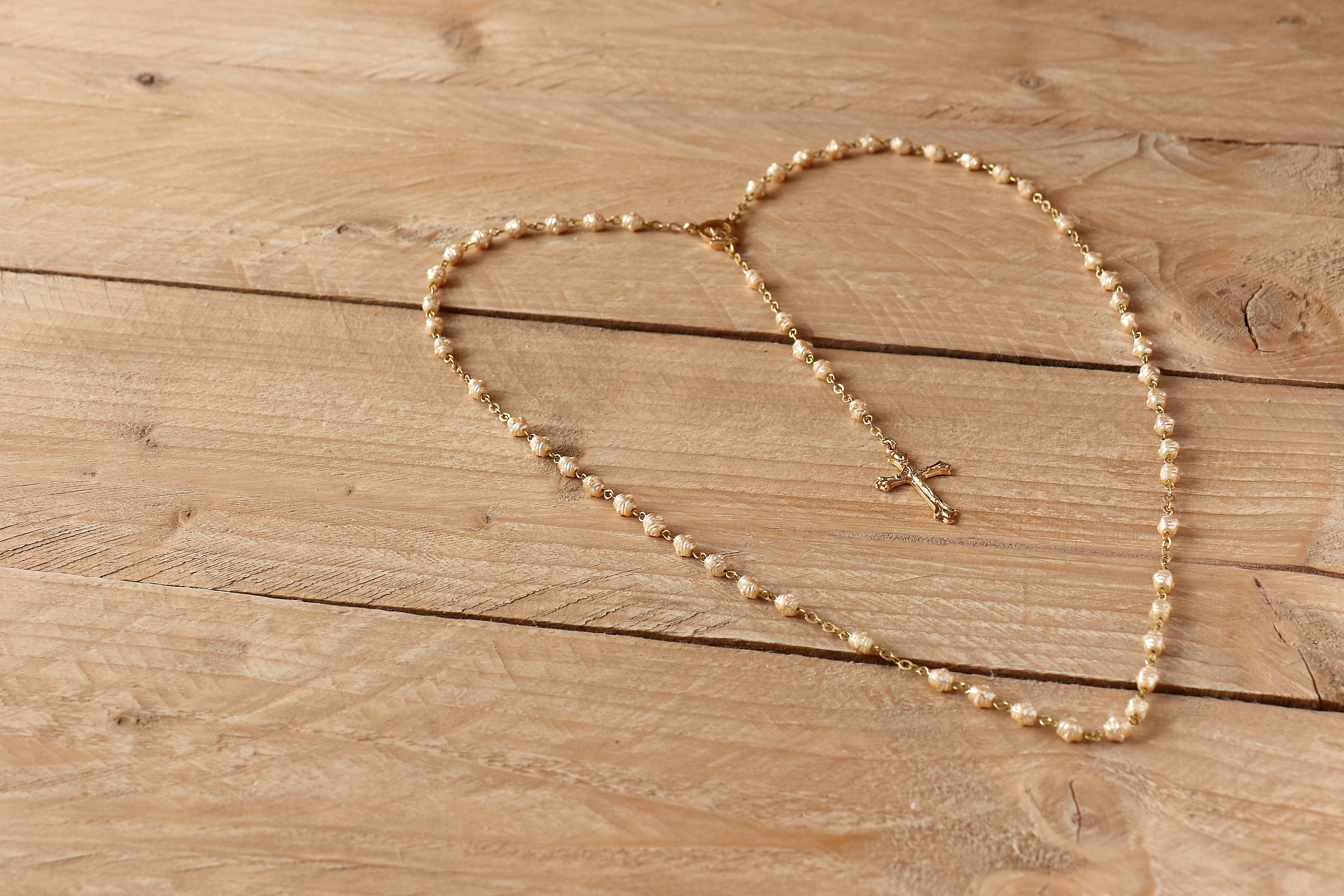 White Rosary on Beige Wooden Surface