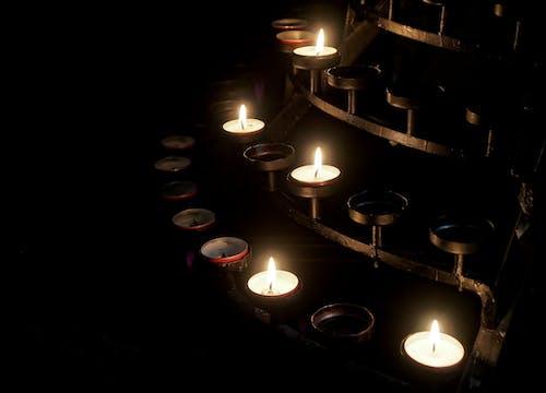 Five Lit Votive Candles on Candle Holder