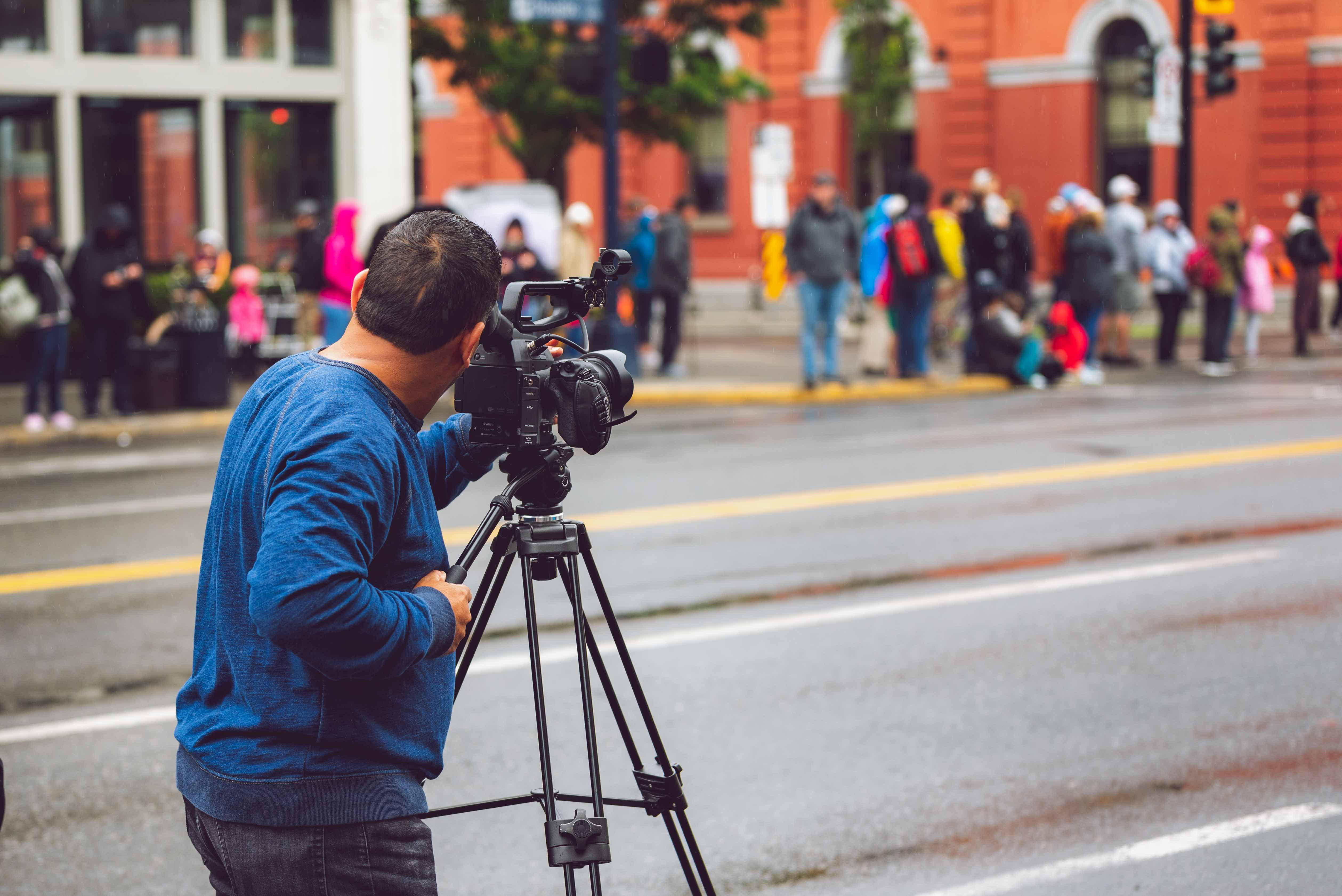Camera Man With Video Camera on Tripod Position by the Street Across People at the Sidewalk
