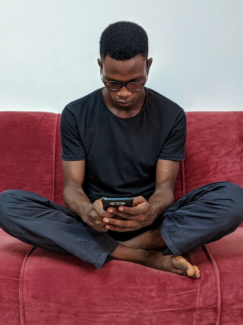 Man Sitting on Red Suede Sofa Holding Black Android Smartphone
