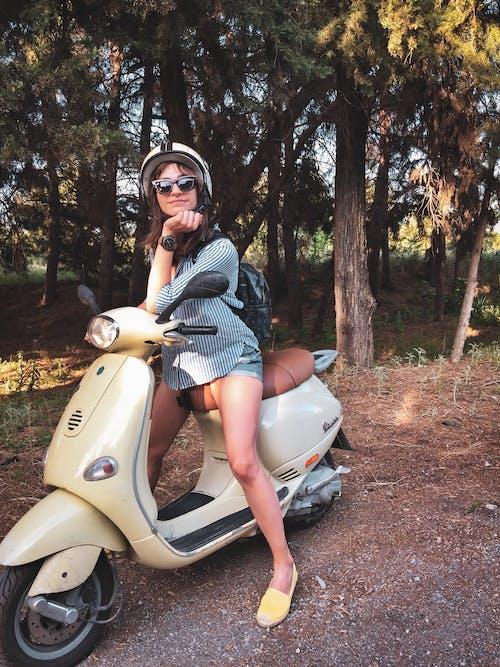 Woman Wears Helmet on Beige Motor Scooter