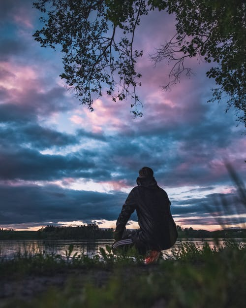 Man Kneeling and Facing Calm Body of Water Under Dramatic Clouds
