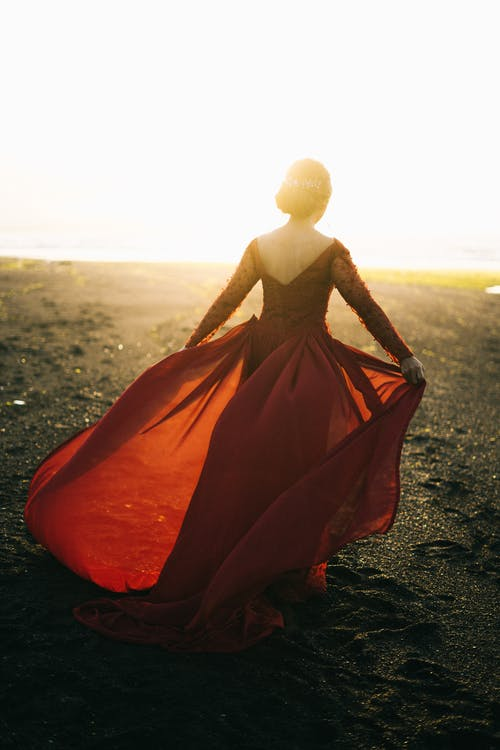 Woman In Red Long Sleeved Dress Walking On Shore