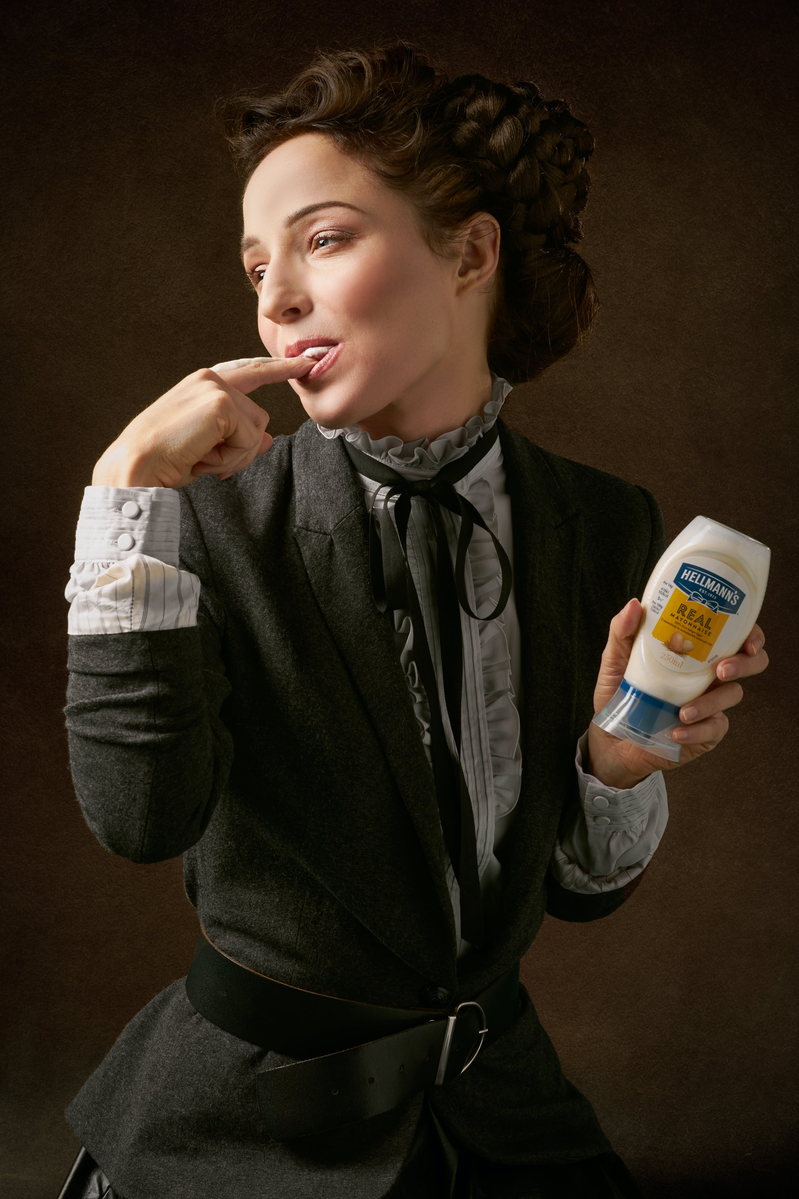 Woman in Black Coat Holding Product Bottle