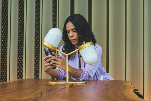 Woman Leaning on Wooden Table Using Smartphone