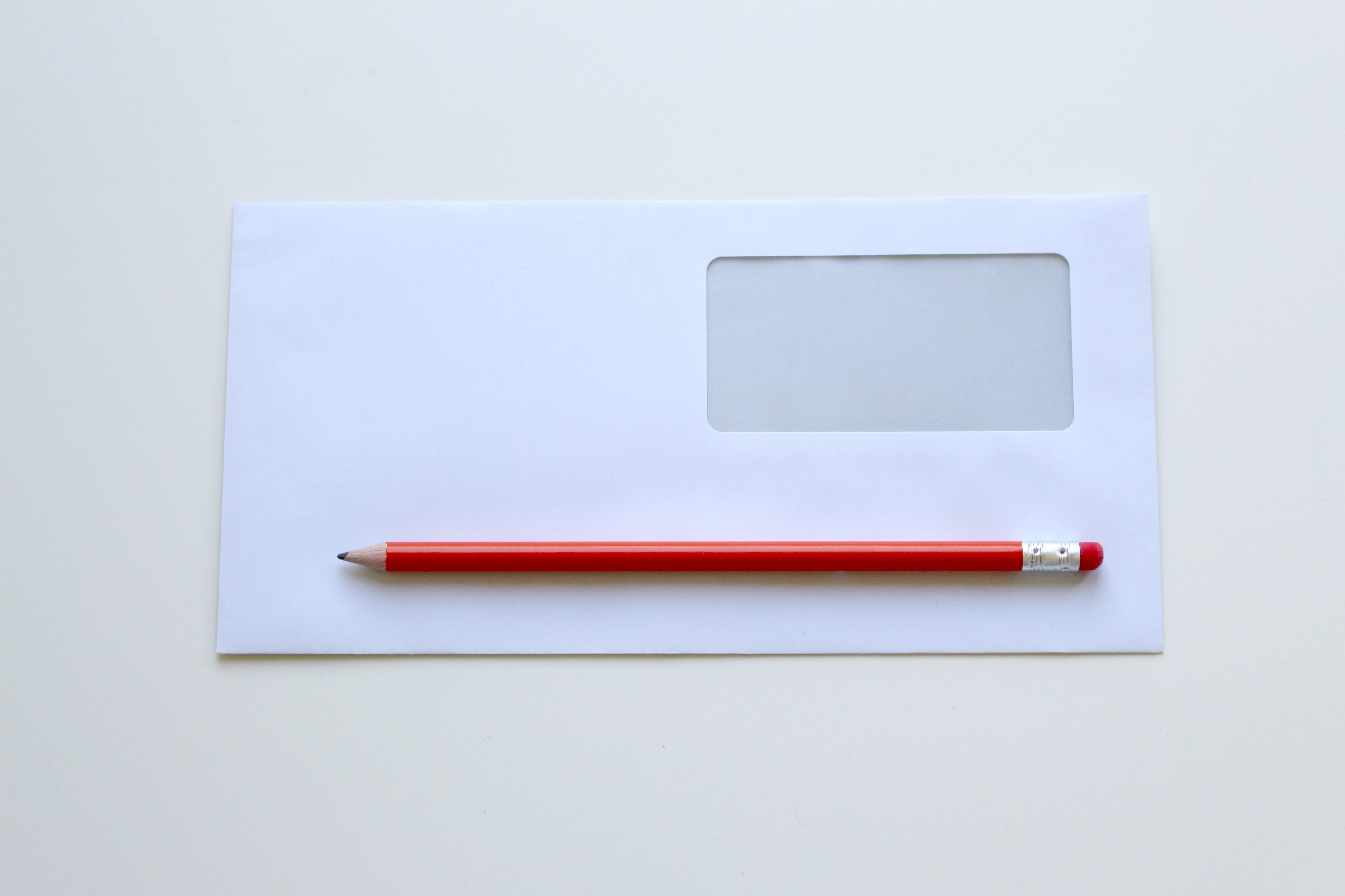 Red Pencil on Top of White Window Envelope