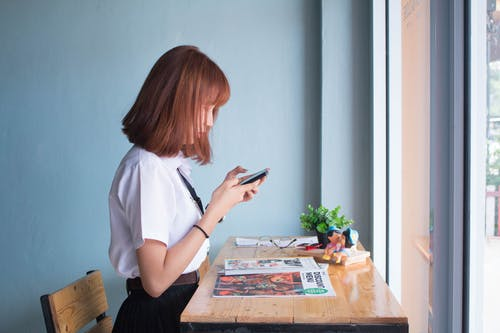 Woman Using Smartphone Beside Table