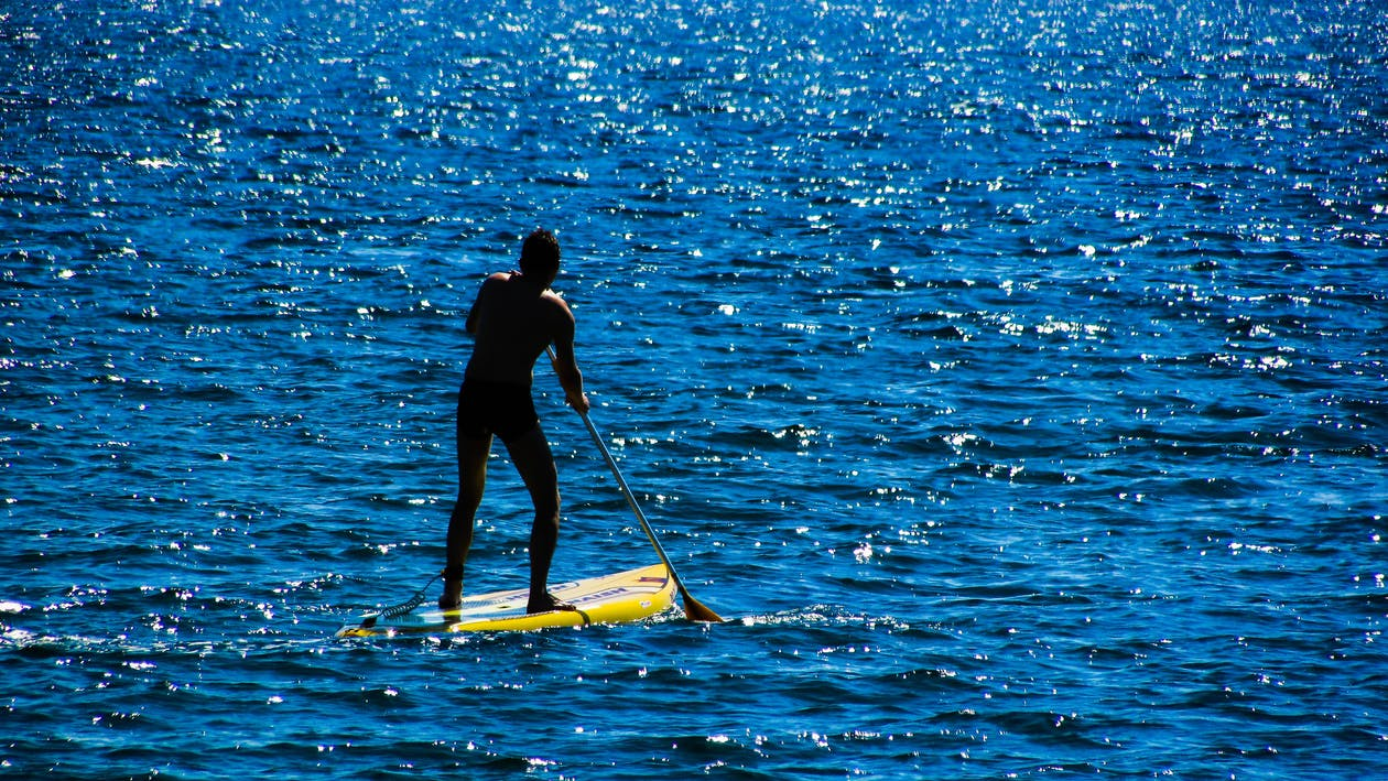 Person Paddling While Standing on Yellow Paddleboard