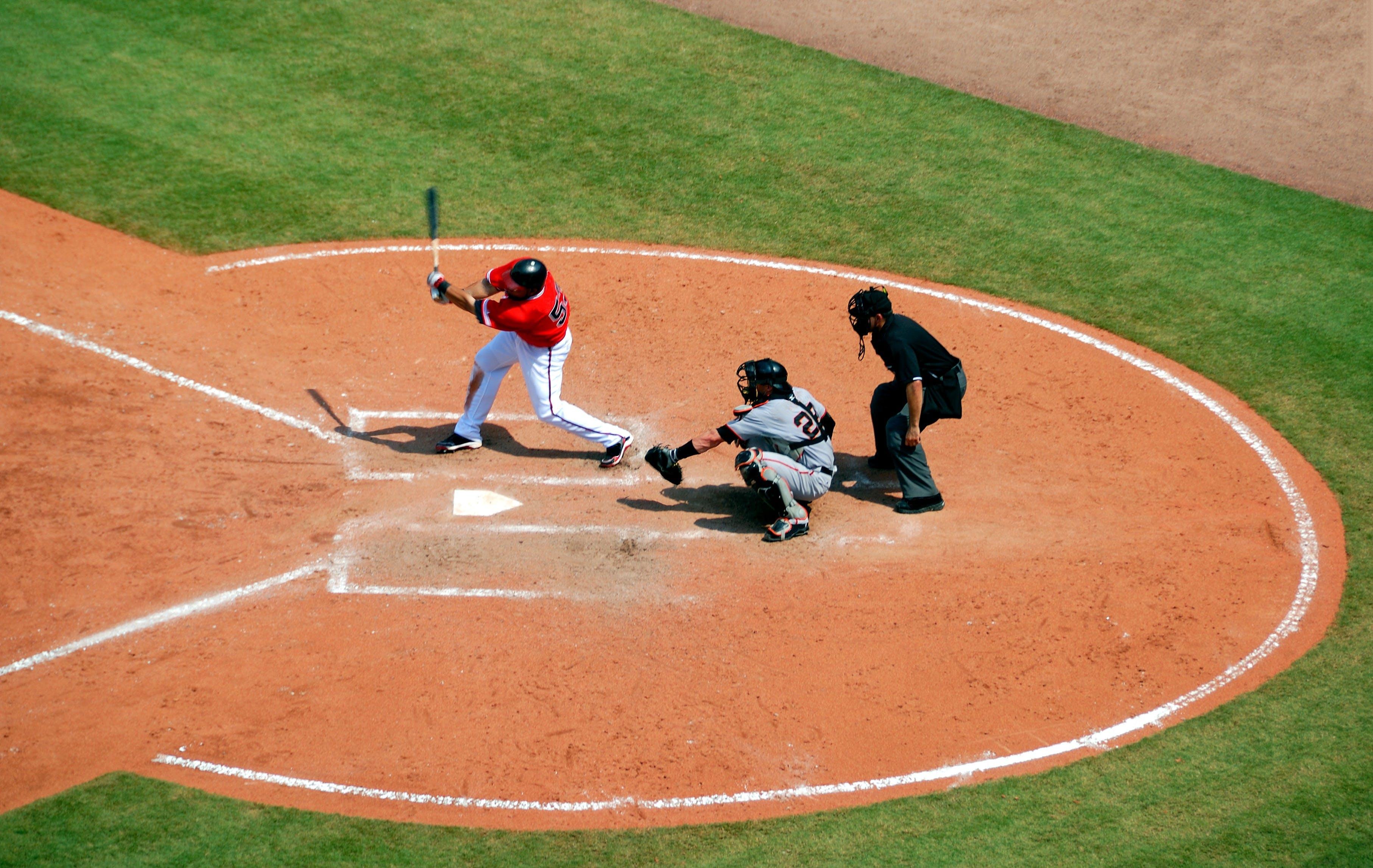 Baseball Player Standing on Baseball Stadium With Two Men