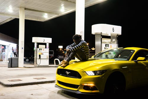 Photo of Man Sitting on Hood of Yellow Ford Mustang Parked at a Gas Station