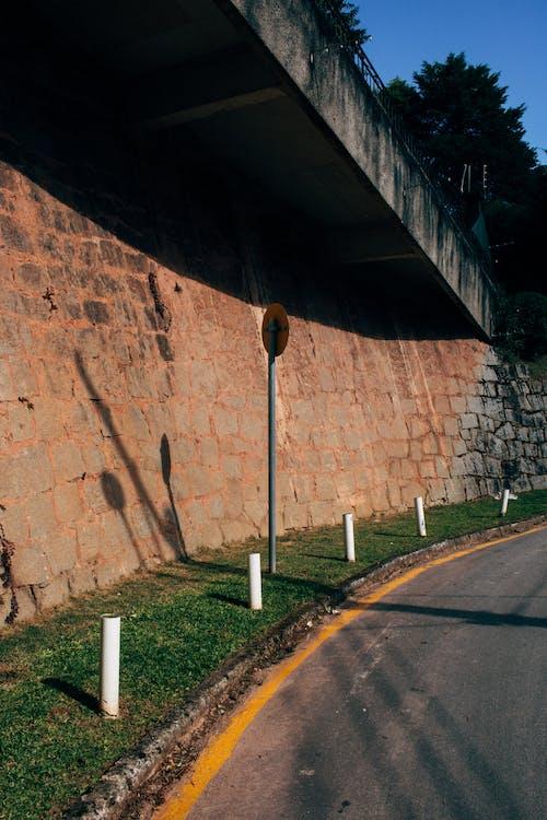 Empty Concrete Road Near Brick Wall