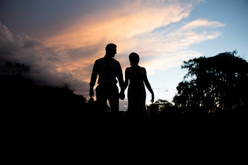 Silhouette Photography Of Woman And Man Standing Near Trees