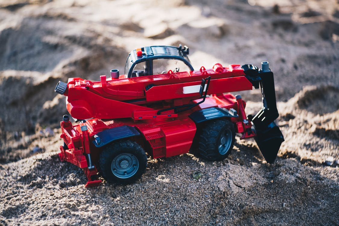 Shallow Focus Photo of Red Front-loader Toy on Gray Sand